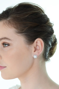 A model with green eyes wears a simple stud earring with a white background