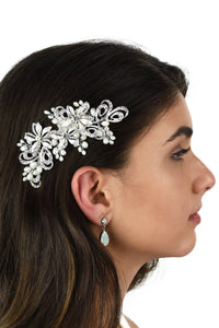 A side view of a models head wearing a silver side comb with a white background