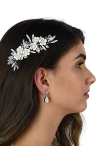 Dark Haired model wears a small silver comb with white opal stones against a white background