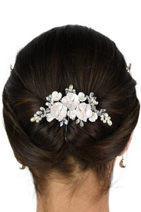 The back of a dark haired model wearing a small pale pink flower comb in an up style hairdo