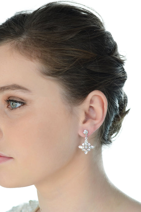 Green eyed dark hair model wears a simple drop earring with a white background