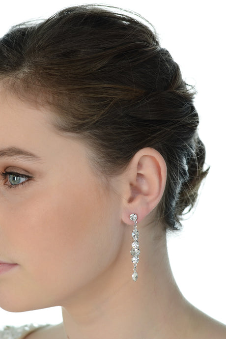 A model wears a long thin bridal earring with a white background