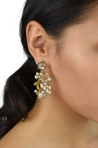 Model wears a gold hoop shape earring in her ear and she has dark hair