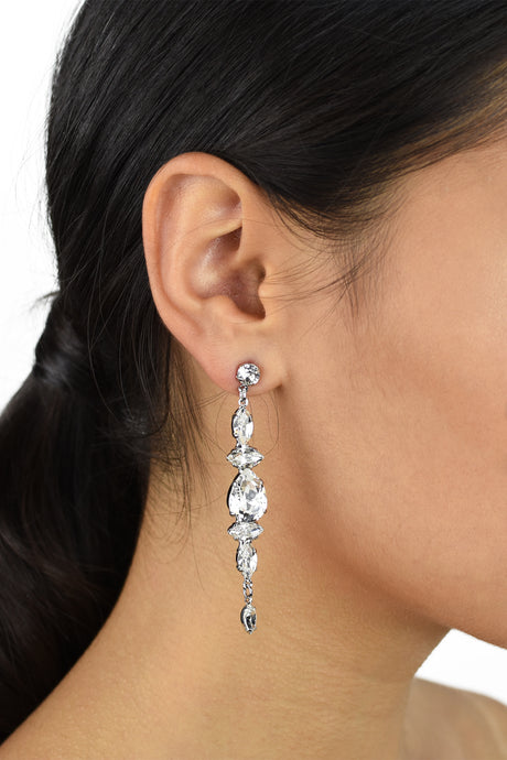 A bride with dark hair wears a long drop Swarovski crystal earring.