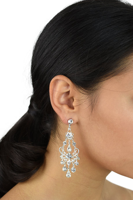 Black haired bride wears a long silver chandelier earring with a white background