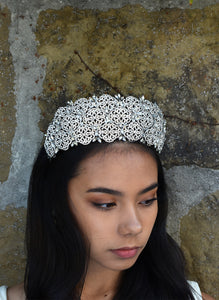 Very high Bridal Tiara with hundreds of tiny crystals worn by a dark hair bride with a stone wall backdrop