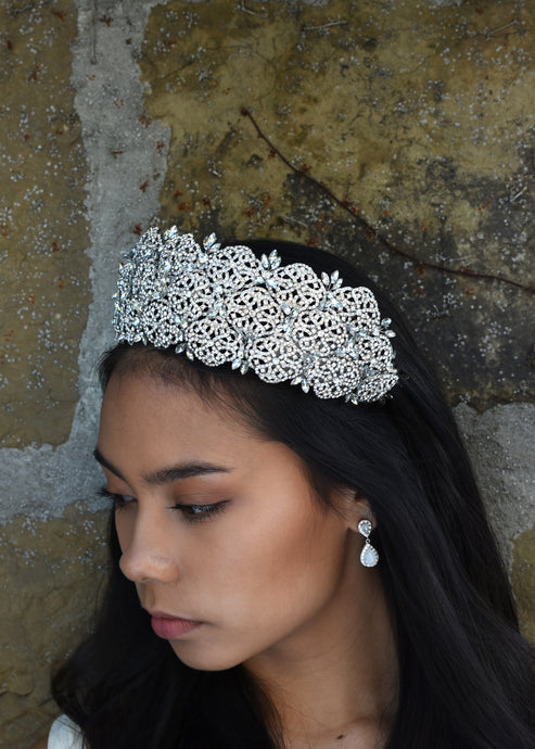 A very high crystal tiara worn by a dark haired bride with a stone wall behind her.