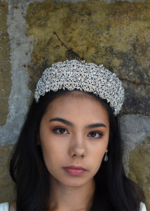 The front view of a bride wearing a high Bridal Tiara covered with tiny crystals with a stone wall background