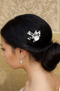 Model Bride wearing a white hair pin in her dark hair with a stone wall background