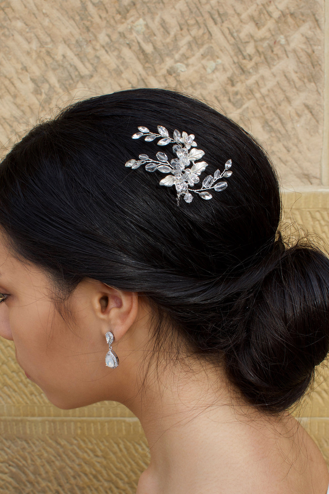 A model Bride with dark hair wears a small silver hairpin in her dark hair with a stone wall background