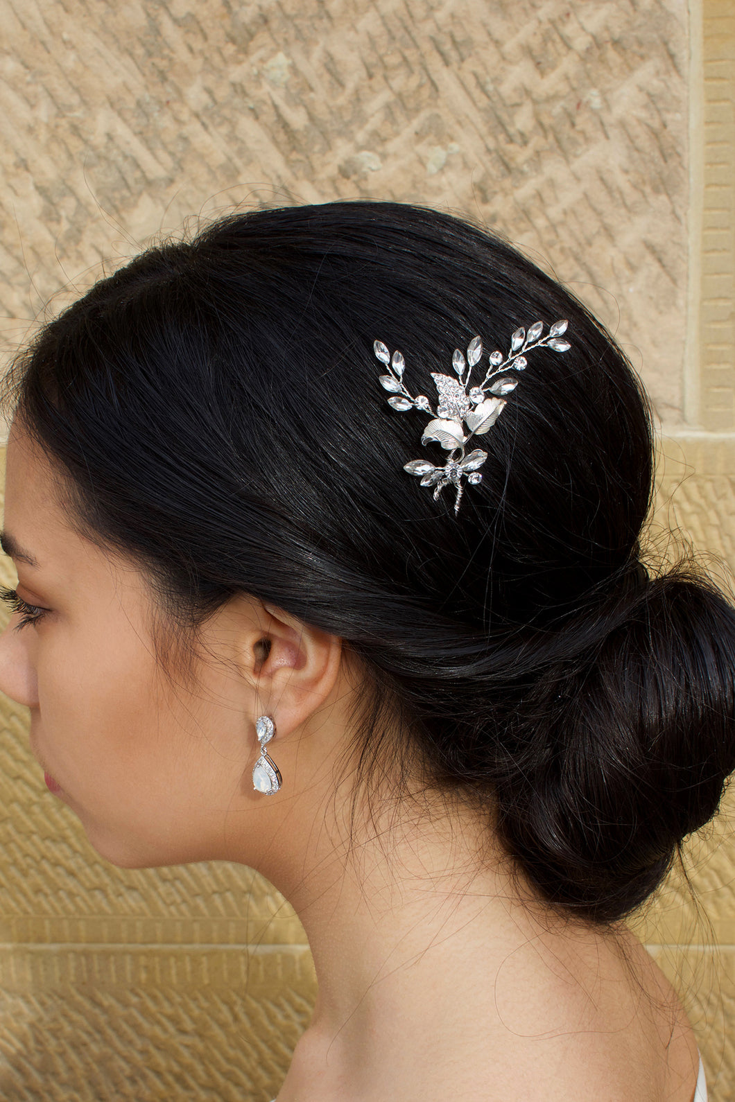 A Dark hair model wears a Silver Bridal Hairpin in the side of her hair with a stone wall background