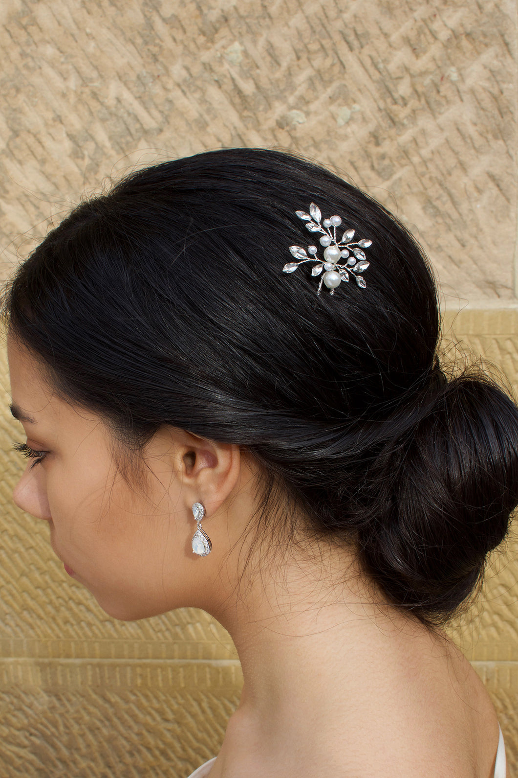 A black haired model wears a pearl and crystal hairpin with a sandstone background