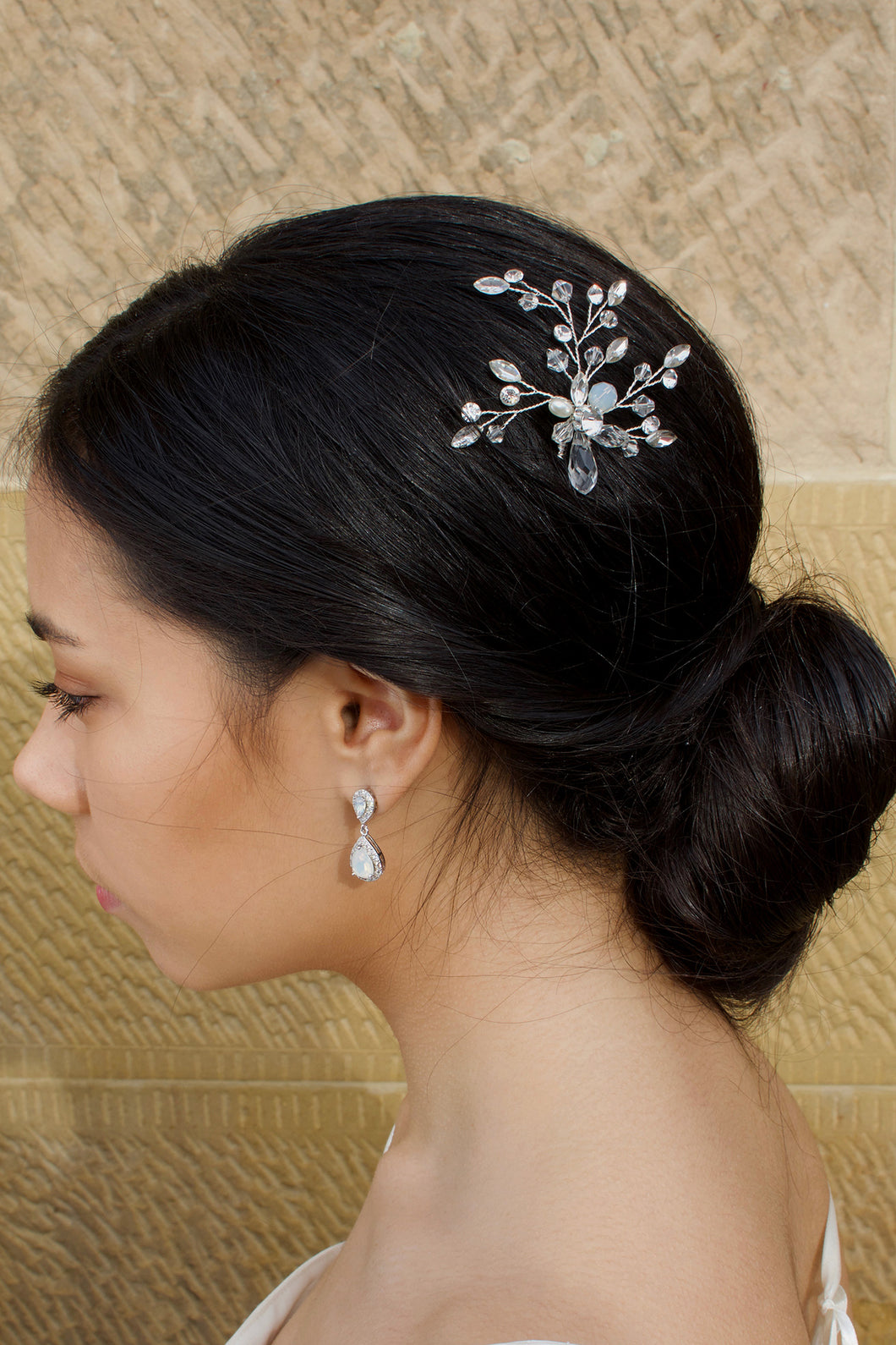 A dark hair Bride wearing a silver hairpin with pearl and white opal with a sandstone wall backdrop