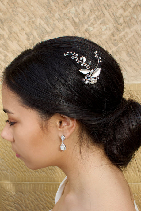 A bride wears a Silver hair pin in her dark hair with a stone wall background