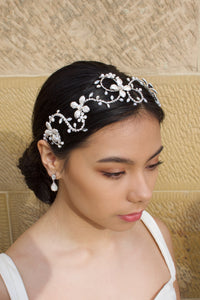 Dark Hair model wears a silver headband with pearls with a stone wall background