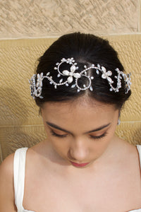 Head down model wears a silver bridal headband with pearls with a stone wall background