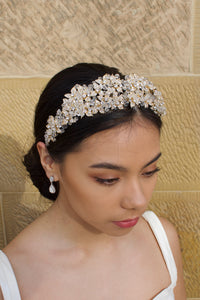 A Gold Tiara with a heavy cover of crystal beads worn by a dark hair model with a stone wall backdrop