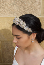 Load image into Gallery viewer, Side view of a bride wearing a gold crown with a thick cover of crystal beads worn by a dark haired bride against a sandstone wall