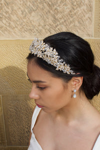 Side view of a bride wearing a gold crown with a thick cover of crystal beads worn by a dark haired bride against a sandstone wall