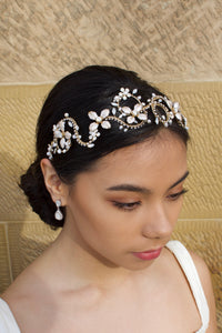 Black hair model wears a gold leaf headband. The model is standing in front of a sandstone wall.