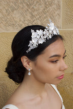 Load image into Gallery viewer, A dark haired bride wears a three pointed flower tiara at the front of her head. Behind is a sandstone wall.