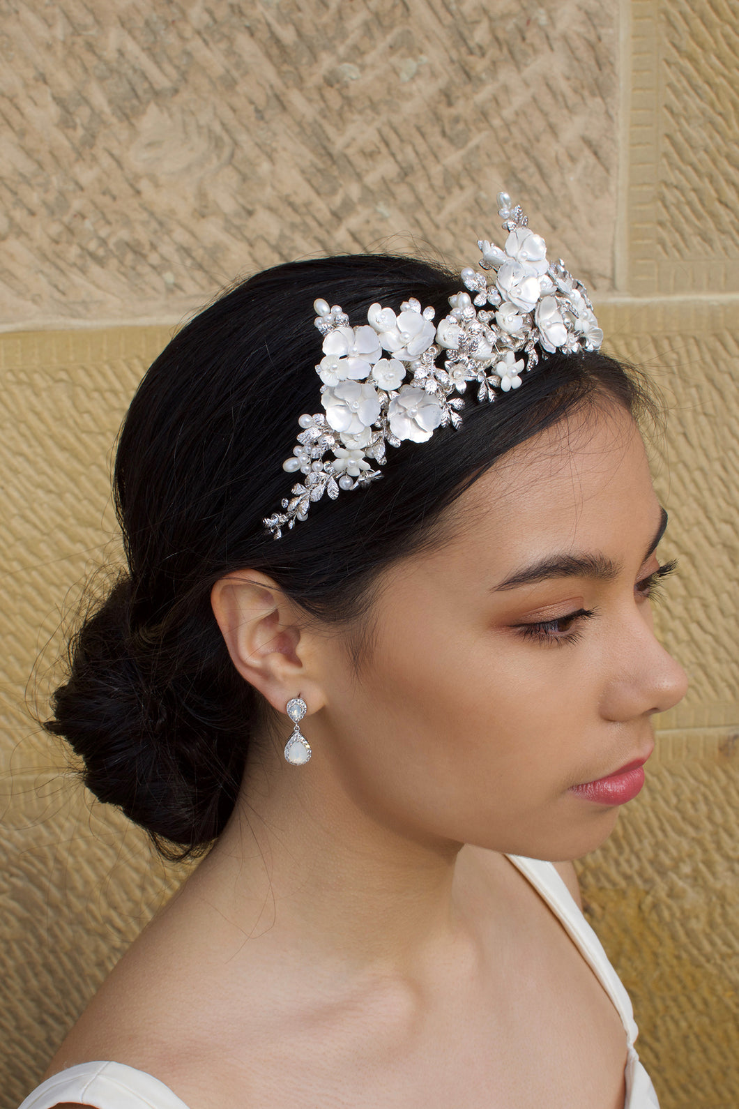 A dark haired bride wears a three pointed flower tiara at the front of her head. Behind is a sandstone wall.