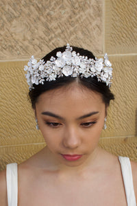 A Black  haired bride wears a three pointed silver flower tiara at the front of her head. Behind is a sandstone wall.
