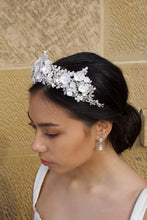 Load image into Gallery viewer, A side view of a dark haired bride wears a three pointed flower tiara at the front of her head. Behind is a sandstone wall.