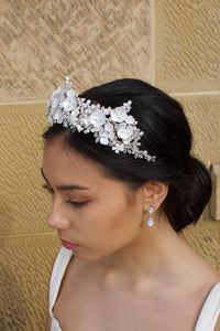 A side view of a dark haired bride wears a three pointed flower tiara at the front of her head. Behind is a sandstone wall.