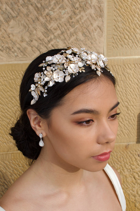 Dark Haired model wears a wide Pale Gold headband of flowers with the background of a stone wall