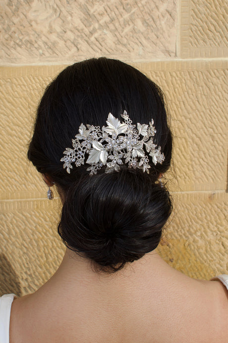 The back of a dark models head with a silver leaf comb with a sandstone wall as background