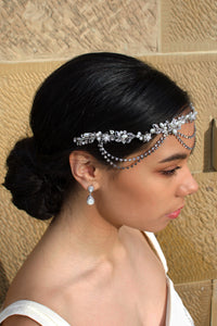 A side view of a bridal vine worn across the forehead of a dark hair bride. With a stone wall behind