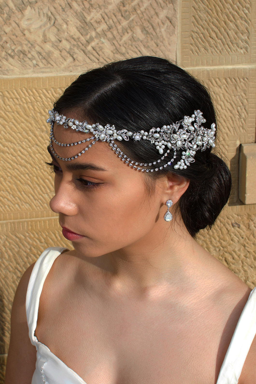 A black haired model wears a bridal vine with loops at the front of the head. With a stone wall background