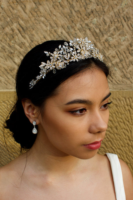 A dark haired model wears a pale gold bridal tiara with clear crystals with a stone wall background
