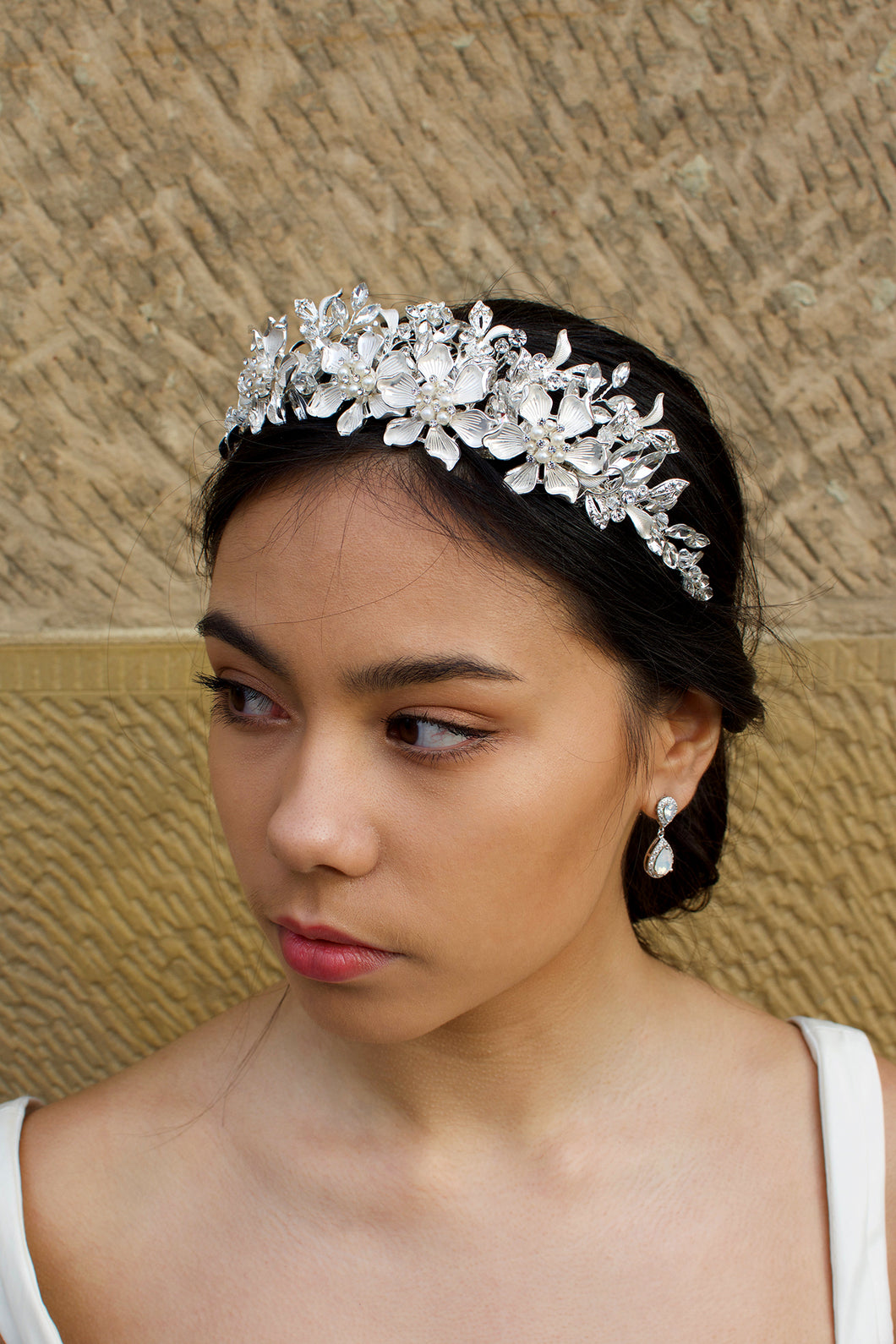 Soft Silver Handmade Tiara with leaves and pearl flowers on a dark hair model in front of an old sandstone wall