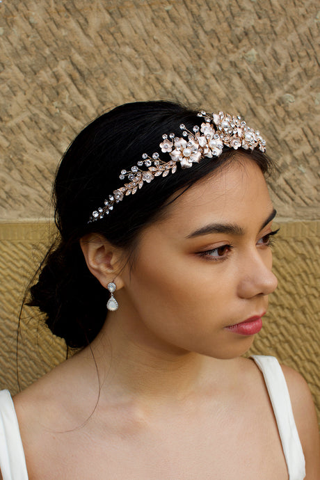 A dark haired model wears a rose gold tiara with pearl flowers against a stone wall background.