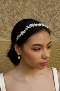 Black hair model wears a narrow silver bridal hairband with shaped stones with a sandstone backdrop