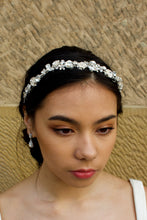 Load image into Gallery viewer, Dark Model wearing a narrow silver headband with metal flowers and shaped stones in silver with a stone wall behind