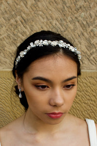 Dark Model wearing a narrow silver headband with metal flowers and shaped stones in silver with a stone wall behind