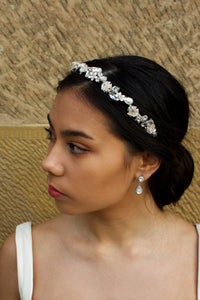 Dark hair Bride looks left wearing a silver flowers and stones headband with a stone wall behind