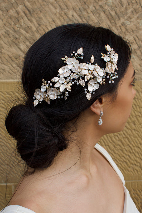 A Dark haired model wears a Pale Gold long side comb with flowers and a small earring