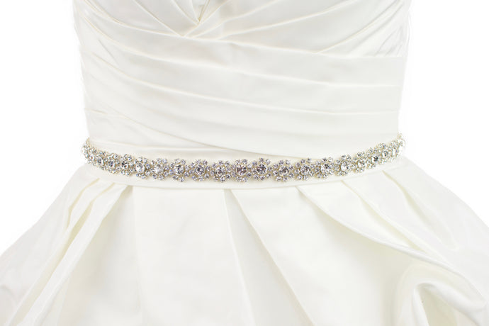 A narrow crystal bridal belt with rings of crystals around the pearls is worn on an ivory bridal gown