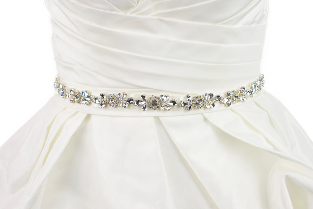 A belt of teardrop shape crystals is around the waist of an ivory satin wedding gown with a white background.