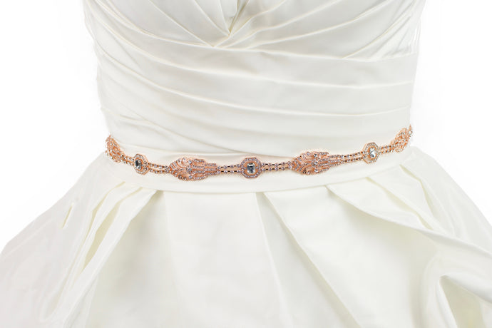 A rose gold narrow bridal belt worn on an ivory bridal gown
