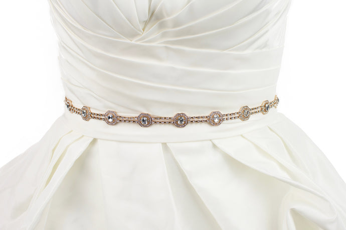 A narrow rose gold belt with crystals is fitted around the waist of an ivory bridal gown with a white background