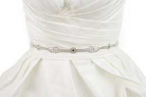 A narrow silver chain bridal belt worn on an ivory wedding gown with a white background
