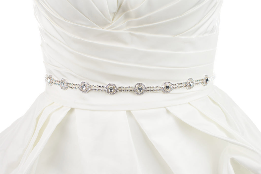 A narrow silver chain bridal belt is fitted around the waist of an ivory bridal gown with a white background