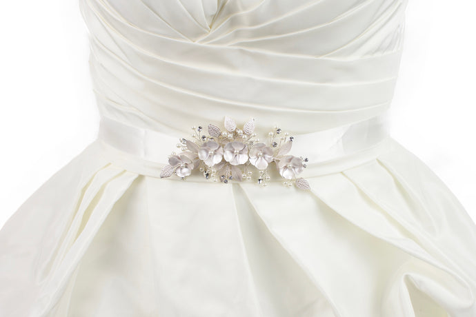 Soft pale pink metal flowers belt on ivory satin ribbon worn on a bridal gown