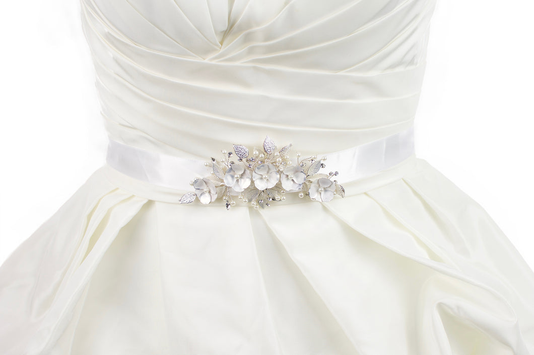 Soft white hand painted flowers on a bridal belt worn on an ivory satin gown