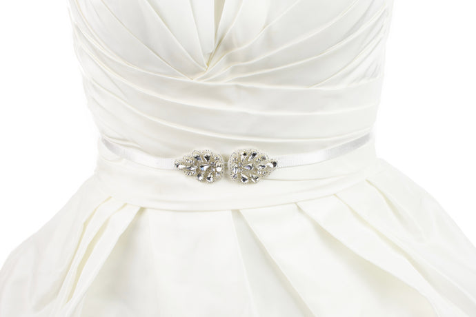 A narrow elastic belt with a small crystal motif at the front worn on an ivory bridal gown